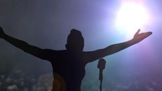 Silhouette einer Sängerin auf Bühne im Scheinwerferlicht