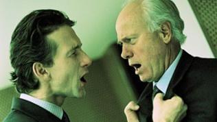 Jüngerer Mann packt älteren verärgert am Anzugkragen