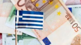 Eine griechische Flagge vor einem Haufen Euro-Scheine.