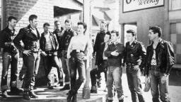 """Filmszene aus """"Der Wilde"""" - Britches (Yvonne Doughty, Mitte) versucht den Bandenführer des Black Rebel Motocycle Clubs Johnny (Marlon Brando, 2.von links) zu beeindrucken."""