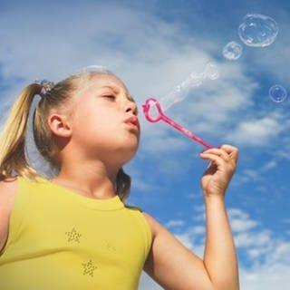 Ein kleines Mädchen macht Seifenblasen (Foto: Getty Images, Getty Images, SWR)