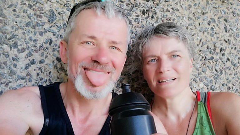 Ein verschwitztes Paar mittleren Alters lehnt lächelnd in Fahrradkleidung an einer Wand, sie hält ihm eine Wasserflasche hin (Foto: SWR, privat)