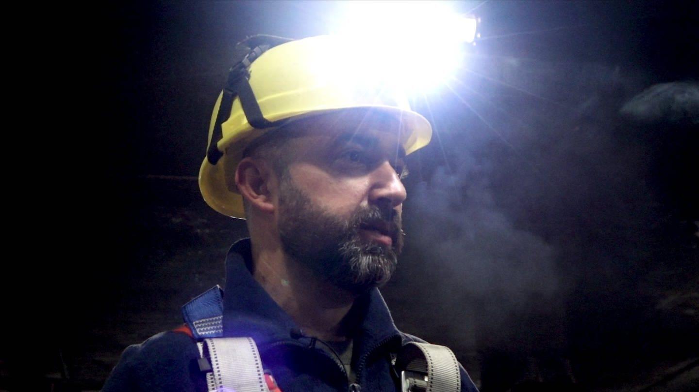 Mann in einem dunklen Tunnel, er trägt einen Schutzhelm mit einer Lampe dran (Foto: SWR)