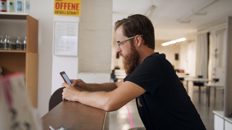Ein Mann mit Bart schaut auf ein Smartphone (Foto: SWR)