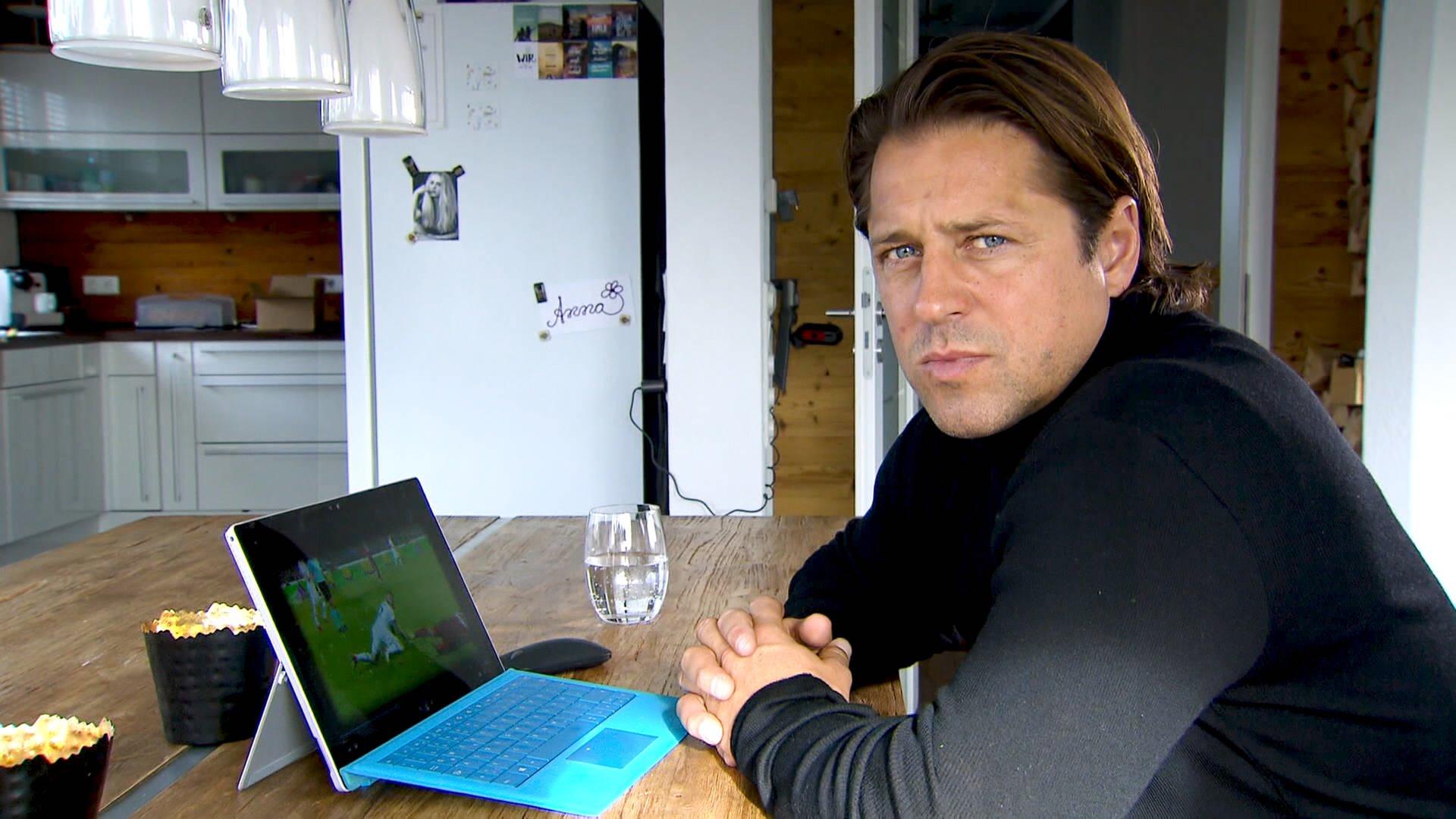 Ein Blonder Mann sitzt am Tisch. Vor sich, ein tablet. Er schaut in die Kamera