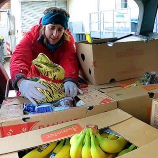 Junge Frau an einem mit Lebensmittelkisten gefüllten Kofferraum (Foto: SWR)