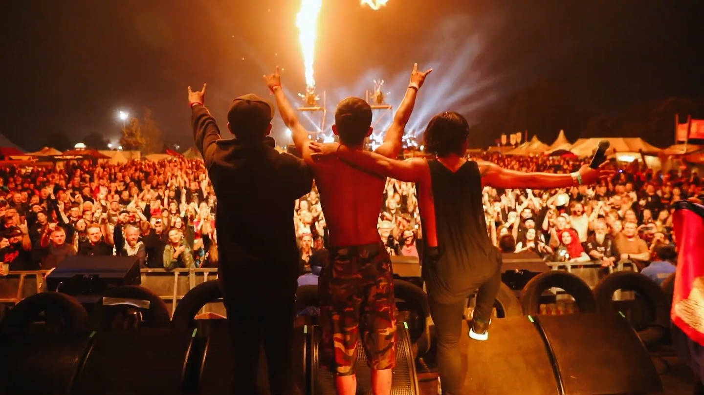 Drei Musiker von hinten, stehen auf der Bühne in Wacken, halten sich in den Armen, Publikum jubelt (Foto: SWR)