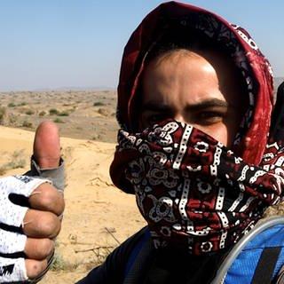 Mann steht in Wüste und hält den Daumen hoch (Foto: Miran Hussain)