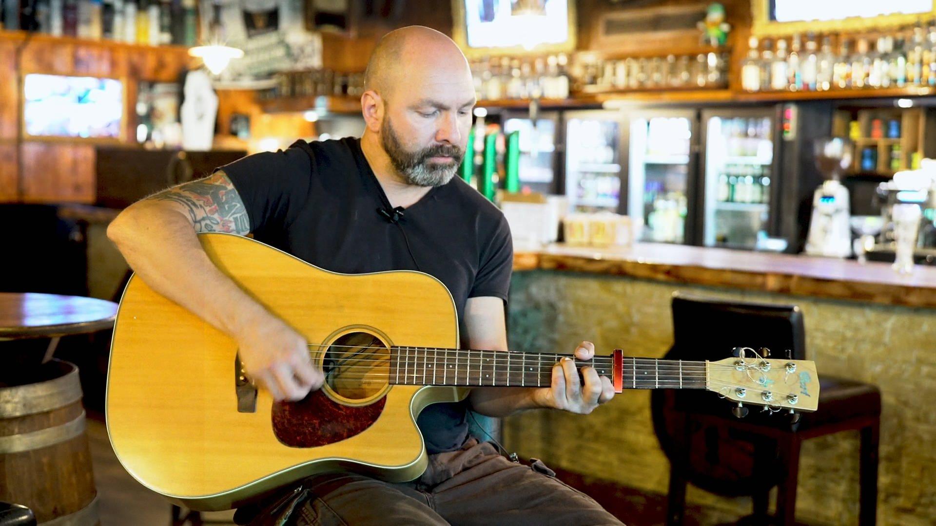 Taio ist Straßenmusiker und spielt Gitarre in einer Bar