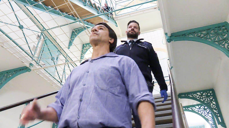 Tjorben geht hinter einer anderen männlichen Person eine Treppe in der JVA Freiburg herunter (Foto: SWR)