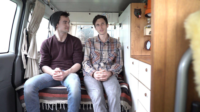 Zwei junge Männer sitzen in einem Bus nebeneinadner und unterhalten sich (Foto: SWR)