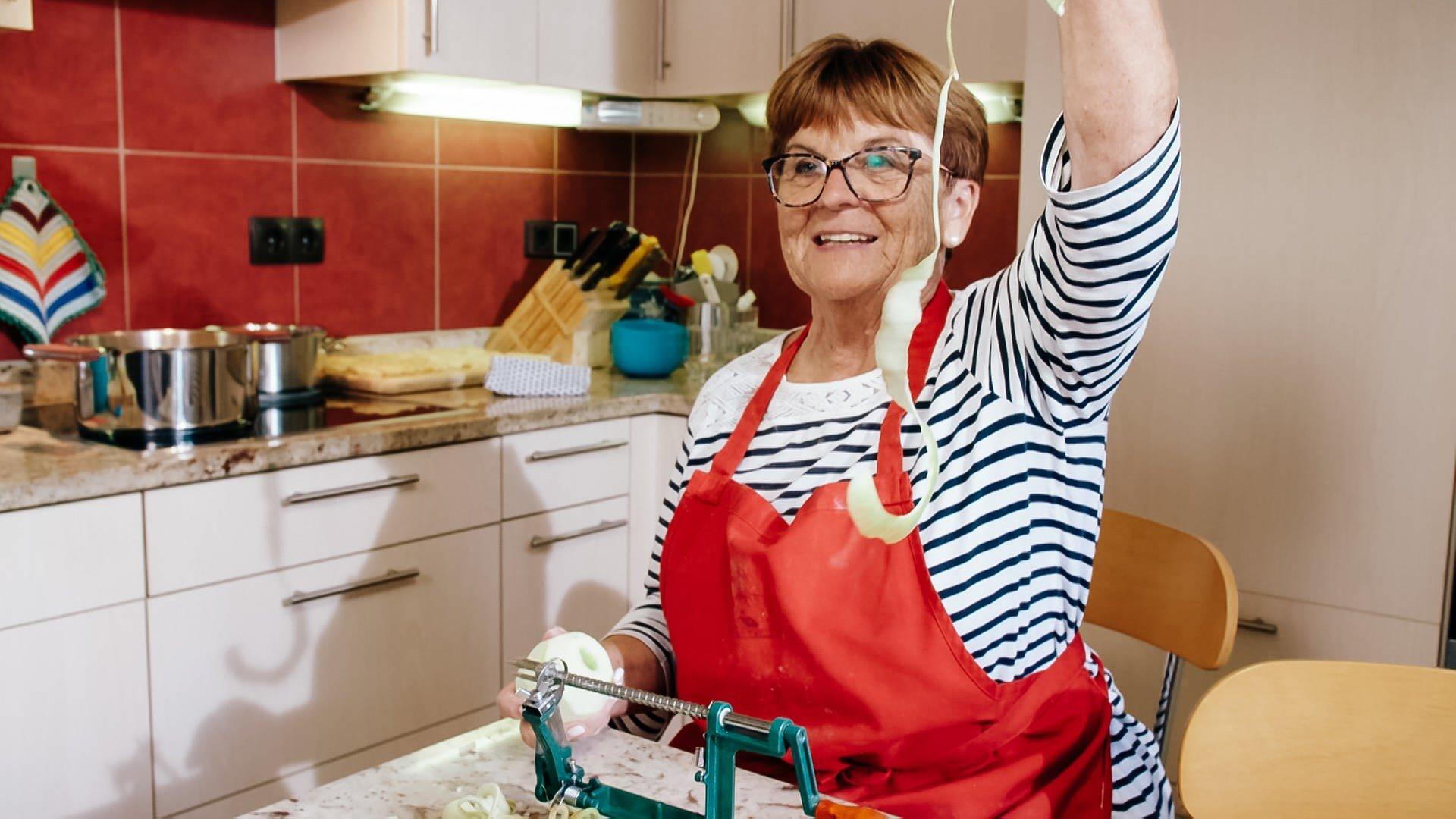 Oma Margarete hält eine Apfelschale hoch, die ihre Heiratsfähigkeit bescheinigt