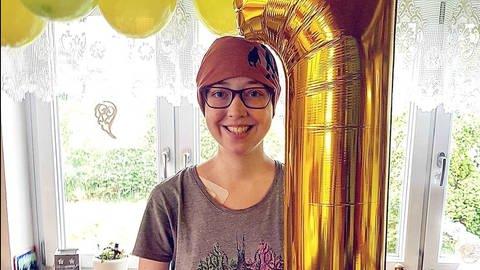 Junge Frau mit goldenem Geburtstagsluftballon in Form einer 1 (Foto: SWR)