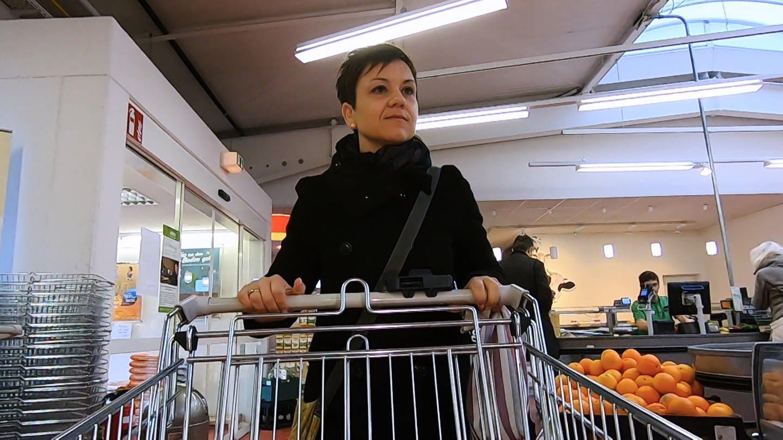 Anja schiebt ihren Einkaufswagen durch den Supermarkt