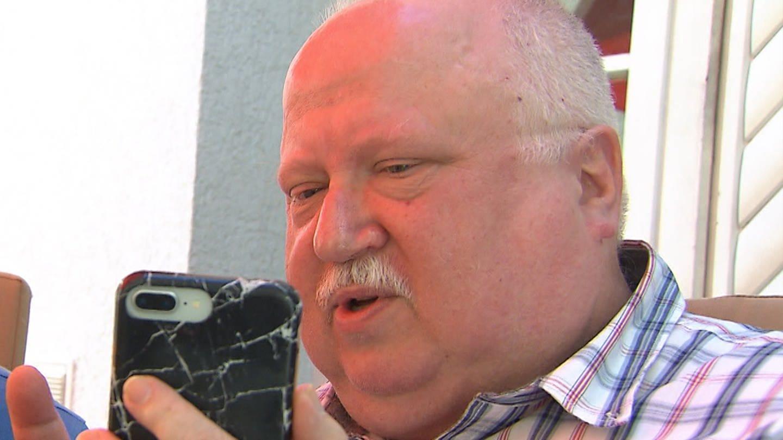 Älterer weißer Mann steht mit Handy in der Hand vor Haus. (Foto: SWR)