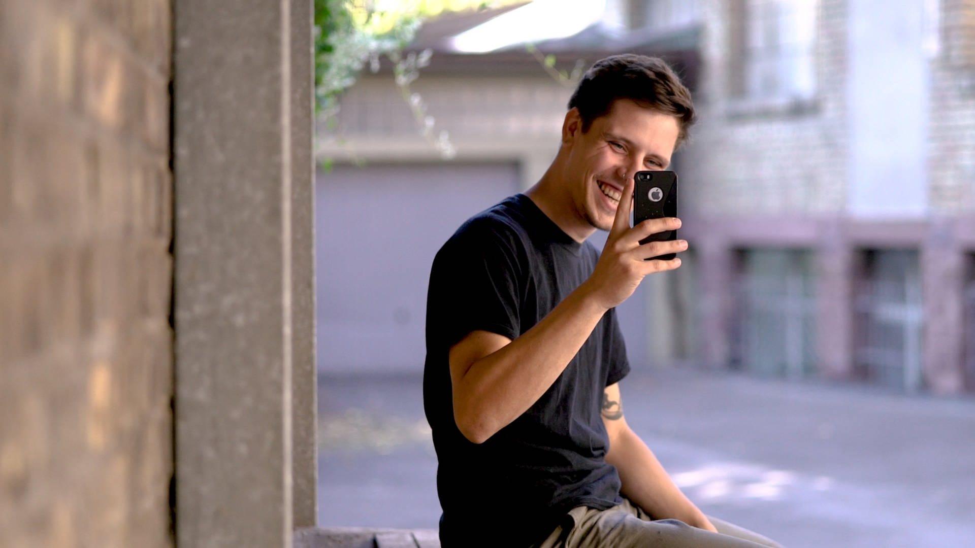 Tomasz lacht und fotografiert mit dem Handy den Kameramann