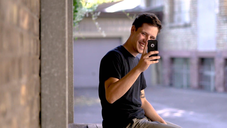 Tomasz lacht und fotografiert mit dem Handy den Kameramann (Foto: SWR)