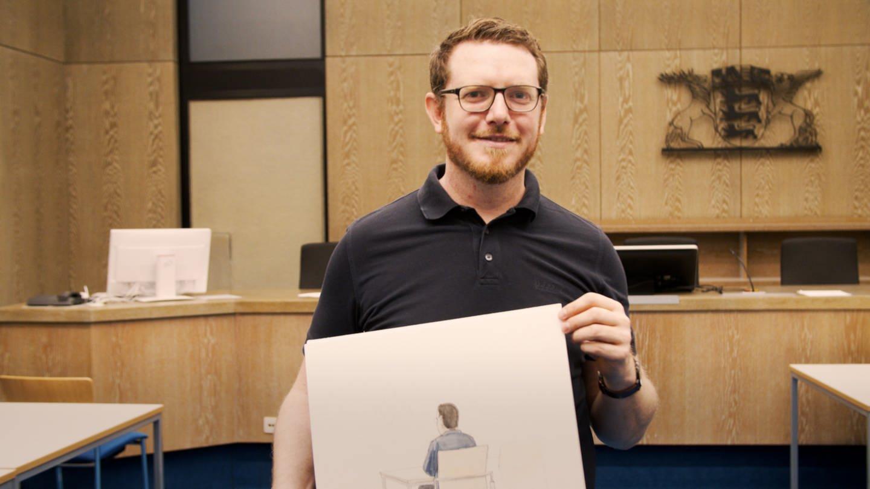 Gerichtszeichner Martin im Gerichtssaat mit Zeichnung (Foto: SWR)