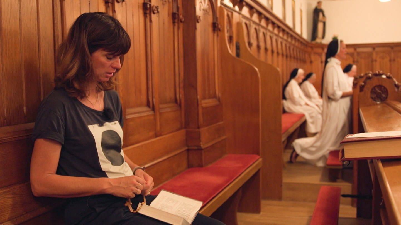 Frau in Tshirt und Jeans betet zwischen Nonnen Rosenkranz im Kloster (Foto: SWR)