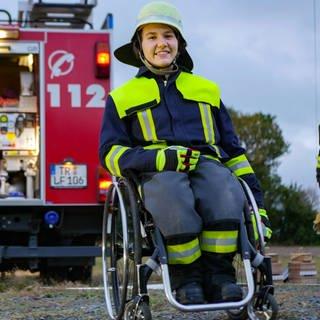 Junge Frau im Rollstuhl vor Feuerwehrauto (Foto: SWR)