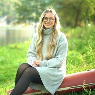 Junge Frau am Flussufer auf dem Rumpf eines Ruderbootes sitzend (Foto: SWR)