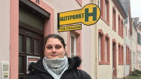 """Junge Frau in schwarzer Winterjacke vor einem Hauseingang mit dem Schild """"Haltepunkt Frauen"""" (Foto: SWR)"""