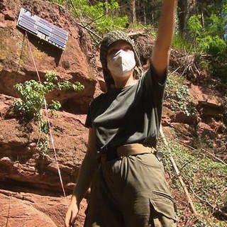 Eine Frau steht vor einem roten Felsen im Wald (Foto: SWR)