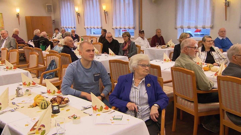 Ein nobler Essenssaal, im Vordergrund sitzt ein junger Mann neben einer älteren Dame an einem Tisch. (Foto: SWR)