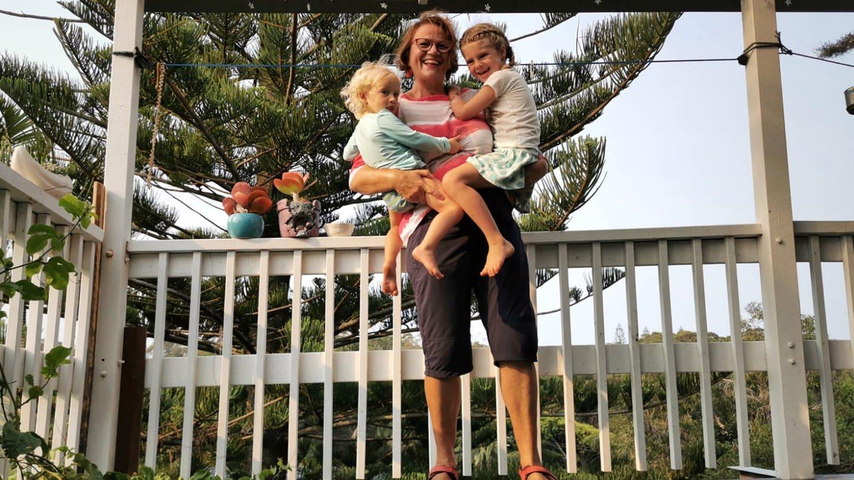 Ältere Dame mit zwei Kleinkindern auf dem Arm auf einer Terrasse. (Foto: Ingrid Steegmüller)