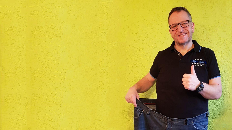 Mann hält eine Jeans vor sich, die doppelt so breit ist wie er selbst (Foto: SWR)