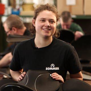 Junge Frau mit ihren Händen auf einem Sattel, der vor ihr auf einer Werkban liegt (Foto: SWR)