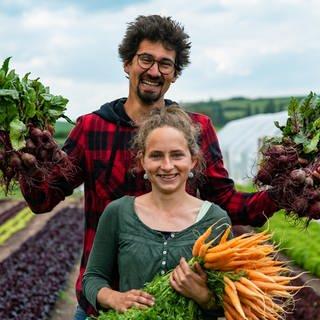 Ein junges heterosexuelles Paar in einem Gemüsegarten mit Gemüse in den Händen (Foto: SWR)