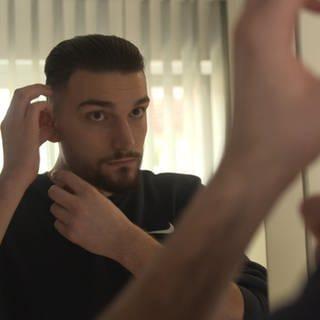 Arianit, ein junger Mann mit Vollbart, steht vor dem Spiegel und setzt sich ein Hörgerät ein (Foto: SWR)