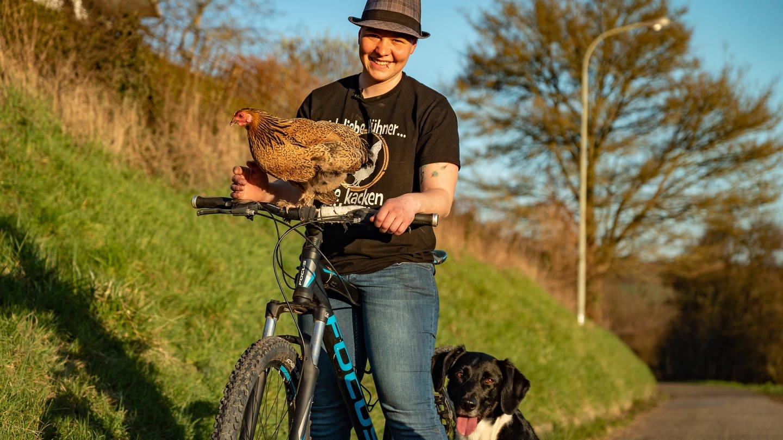 Junge Frau mit Huhn, das auf dem Fahrradlenker sitzt, und einem Hund.