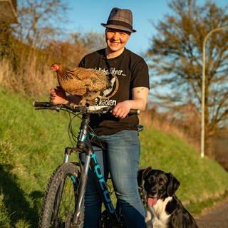 Junge Frau mit Huhn, das auf dem Fahrradlenker sitzt, und einem Hund. (Foto: SWR)