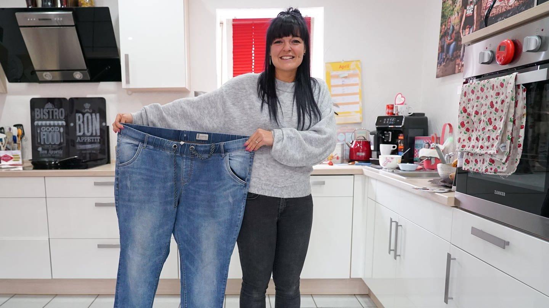 Jessica mit ihrer alten Hose, die ihn nun viel zu groß ist. unge Frau mit schwarzen langen Zopf und Pony, schaut fröhlich in die Kamera