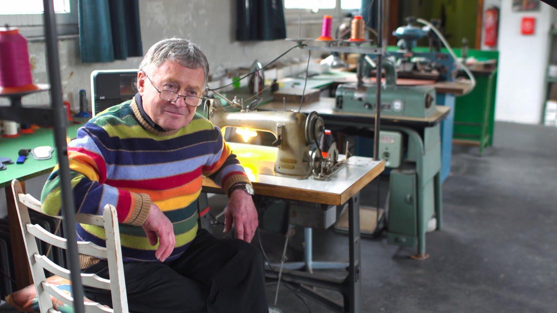 Ein alter Mann sitzt alleine an einer Nähmaschine in einer alten Fabrikhalle
