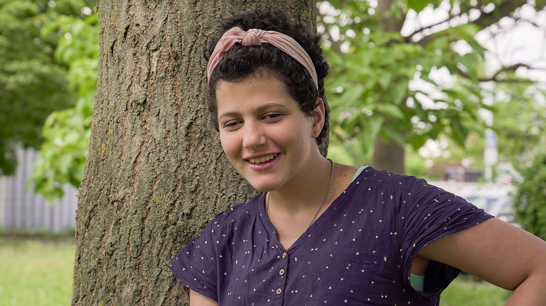 Maja, vor einem Baum. Sie hat ein Haarband in ihren kurzen, braunen Haaren