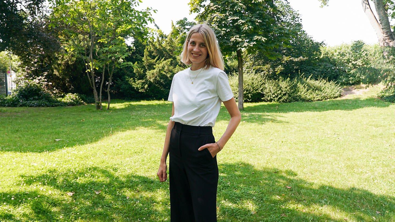 Hannah, Gründerin eines nachhaltigen Modelabels, steht auf einer grünen Wiese.
