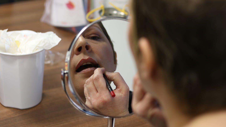 Eine Frau schminkt sich vor dem Spiegel die Lippen. (Foto: SWR)