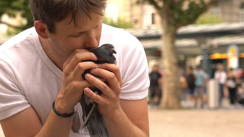 Matthias streichelt eine Taube (Foto: SWR)