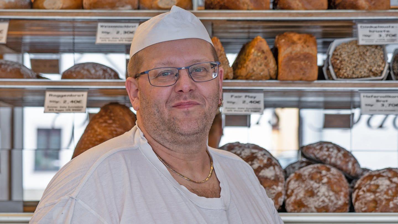 Bäcker mit weißer Mütze vor der Auslage seiner Bäckerei. (Foto: SWR)