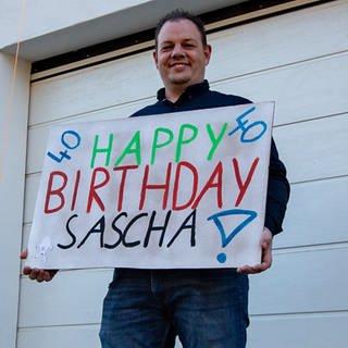 Mann, 40 Jahre alt mit einer Pappe zu seinem Geburtstag in der Hand (Foto: SWR)