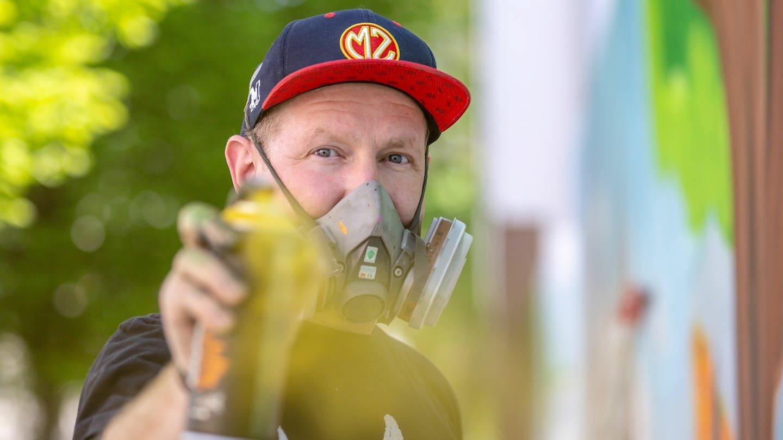 Berufssprayer Leif Möller mit Maske und Spraydose (Foto: SWR)