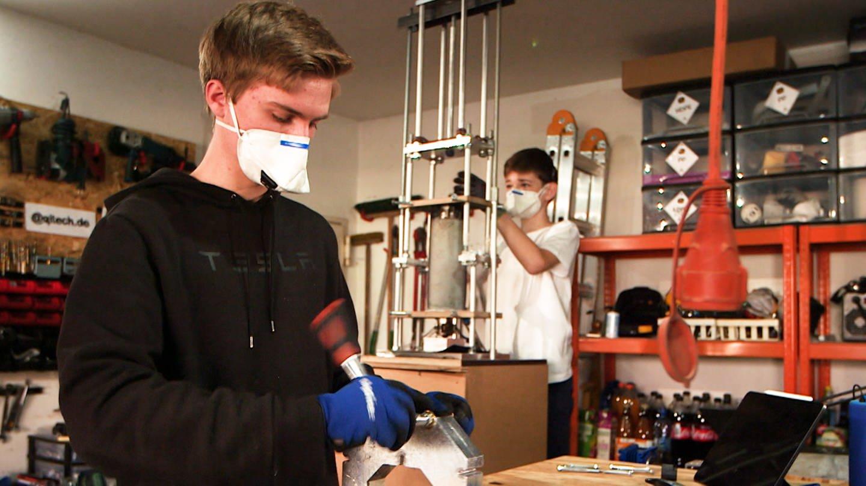 Zwei junge Schüler mit Atemmasken bauen an Maschinen aus Plastikmüll Schutzvisiere für Krankenhäuser (Foto: SWR)