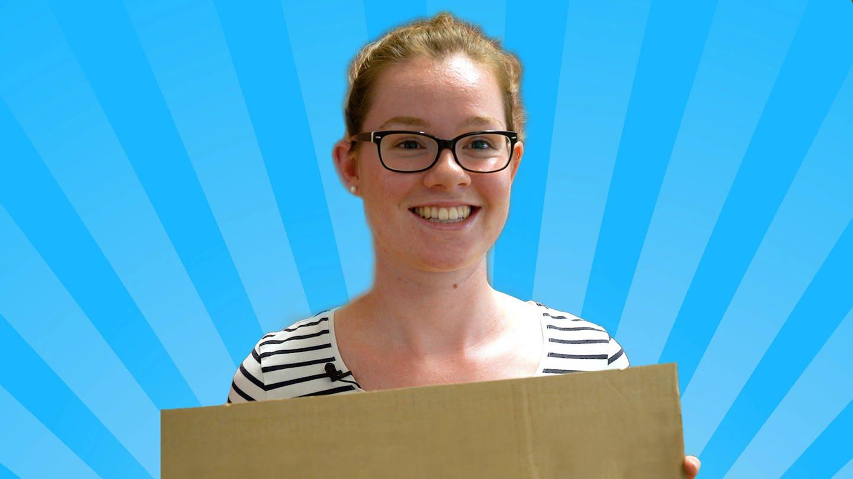 Junge Frau lächelnd mit Pappschild in der Hand