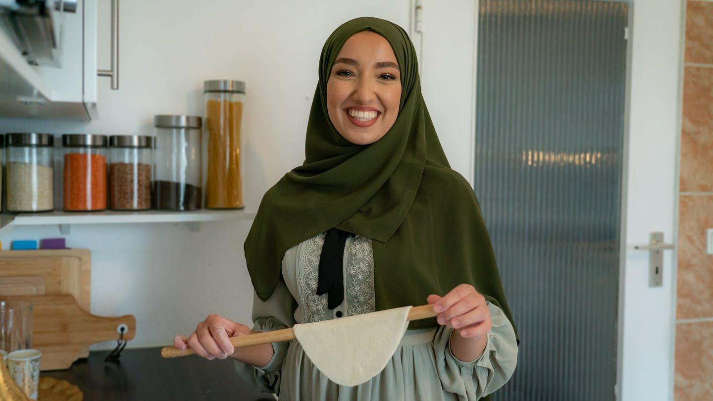Junge Frau mit Kopftuch und einem Holzstab in der Hand über dem ein Stück Teig hängt (Foto: SWR)