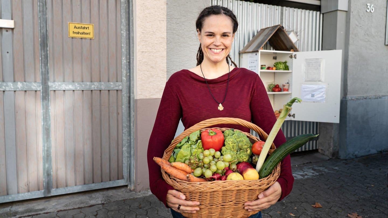 Eva, 30, mit einem Korb voller Lebensmittel in der Hand.