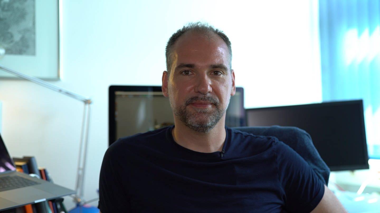 Ein Mann mit blauem T-Shirt und leicht grauem Bart blick frontal in die Kamera (Foto: SWR)
