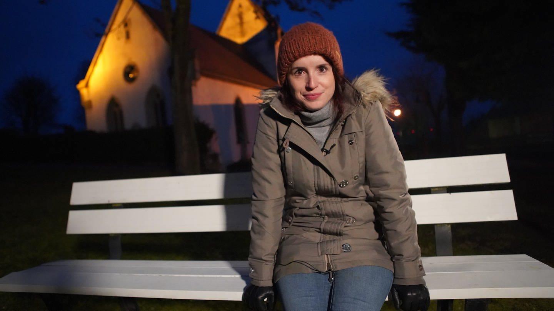 Junge Frau in Winterkleidung auf weißer Bank vor Kirche bei Nacht mit Blick in die Kamera (Foto: SWR)